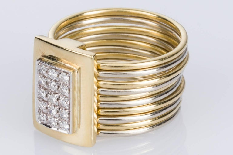 A stunning Damiani Multi Band ring consisting of 10 individual rounded bands alternating between white & yellow gold and each one measuring 1.00 x 1.00mm, with an attached sliding rectangular feature piece set with 15 grain set diamonds. The modern