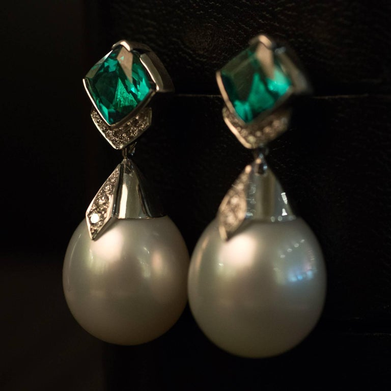 A pair of hand made 18ct white gold Australian South Sea pearl tourmaline and diamond drop earrings. The drop-shaped pearls measure 14mm and have a bright lustre and smooth surface. Set above the pearls to an angle are a pair of half bezel set 6.8mm