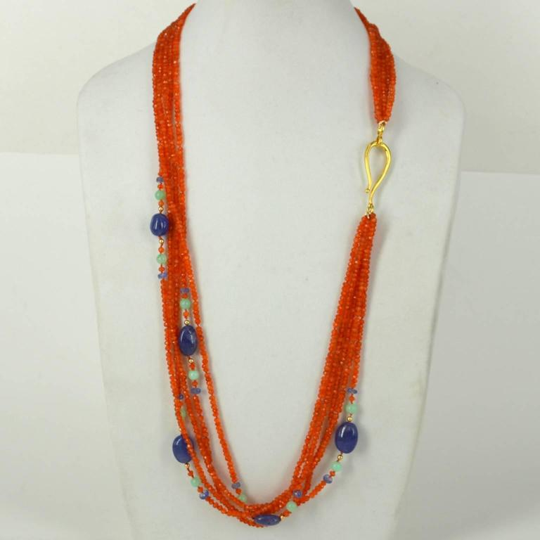 5 Strands of Faceted 4x3mm Carnelian Beads spaced with faceted Tanzanite beads, 6mm Australian Chrsophrase and 5 polished Tanzanite nuggets ranging from 12.8-9.3mm to 16.6x12.2mmon Gold beads are 3mm 14k Gold filled beads and necklace is finished