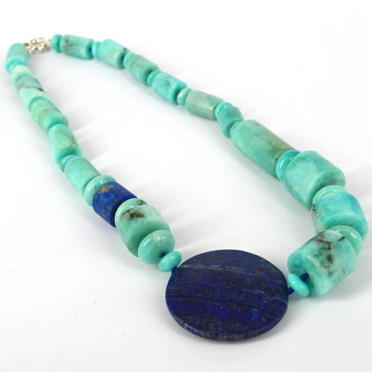 The large off centre 45mm drilled matt Lapis Lazuli bead balances the Peruvian Amazonite Rondels and tubes. Amazonite tubes range from 12x18mm up to 20x18, knotted on Lapis Lazuli coloured thread with a 15mm Sterling Silver Bolt Clasp.  Finished