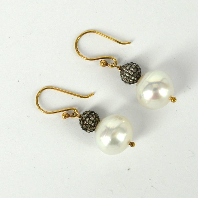 12mm High luster South Sea Pearls with 7mm Pave set Diamond Silver beads. Sheppard and post are 9ct Yellow gold. Earring drop 34mm.