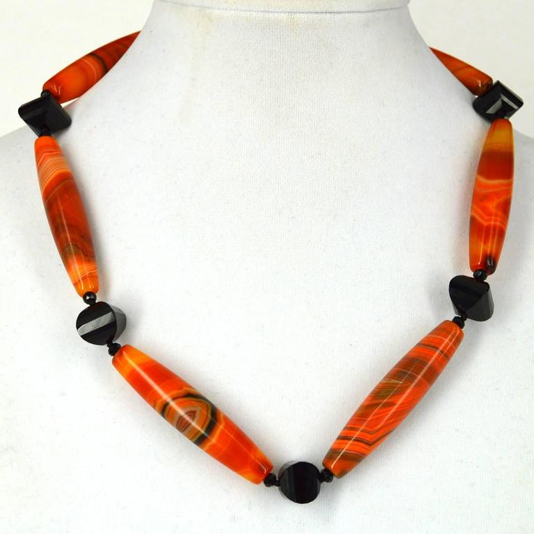 Exceptional quality Orange Banded Agate long olive 55x12mm beads with 12x12mm faceted lantern shaped Onyx beads, finished with a 13mm Gold Plated Sterling Silver bolt ring Clasp. Finished necklace measures 51cm Custom alterations available