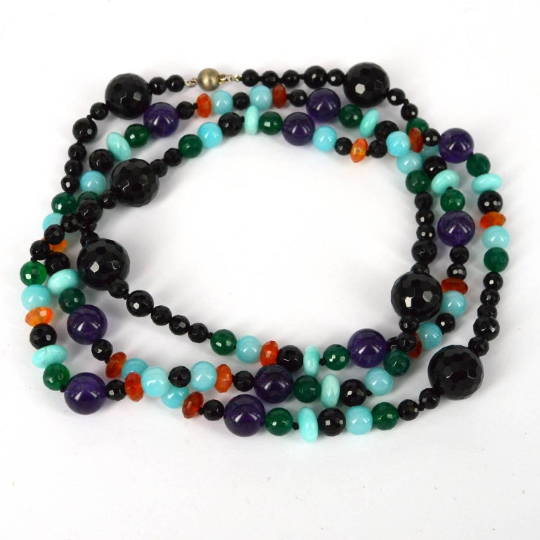 Barcelona long knotted necklace made from 6, 10 and 16mm faceted Onyx, 8mm Faceted Green Onyx, 8x5mm faceted Carnelian, 12mm polished Amethyst, 10x5mm Polished Peruvian Amazonite and 8mm aqua glass beads with a 8mm brushed Sterling silver
