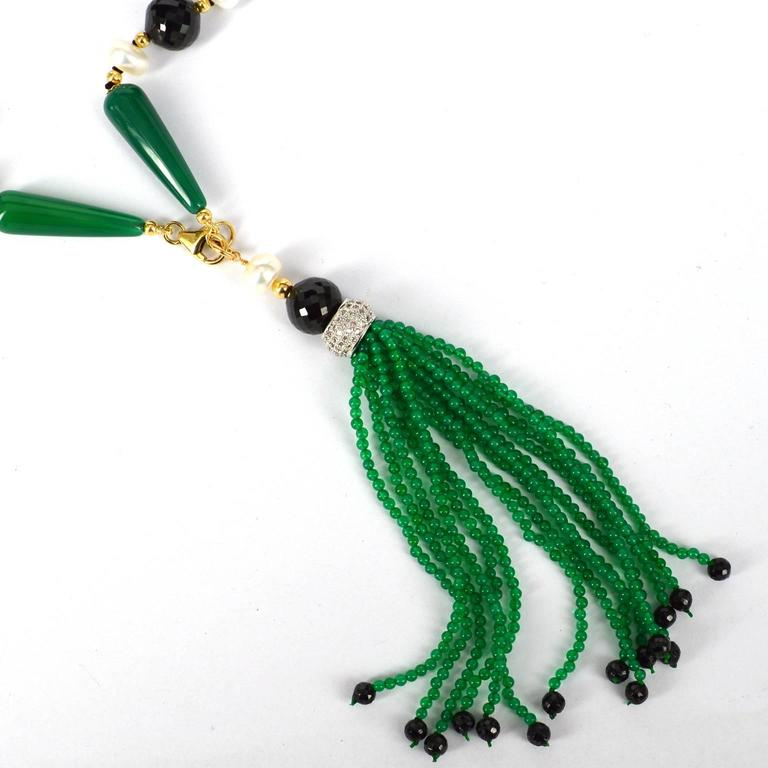 Art Deco style long knotted necklace with 8x28mm polished Green Agate teadrops, 10mm faceted round and 7mm faceted rondel Spinel beads, 8mm Fresh Water Button Pearls. 14k Gold filled 3mm beads, caps and clasp. Tassel is 15 strands of 2mm Green agate