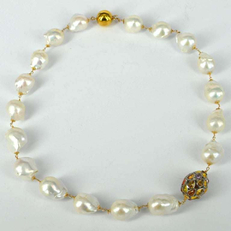 Hand made links join these high quality baroque Fresh Water Pearls 13x18mm graduating to 18x22mm with a Sterling Silver 23x17mm multi colour Sapphire bead. Links and Bead caps are 14k Gold Filled, Sapphire bead is Sterling silver and the clasp is