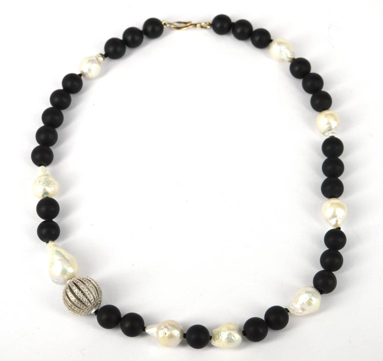 Asymmetrical statement black and white necklace. Matt 10mm black Onyx round and 15mm Fresh water Baroque pearls with a stunning 19cm rhodium plate brass CZ feature bead.  Hand knotted on black thread. Length of necklace 48cm with Sterling Silver