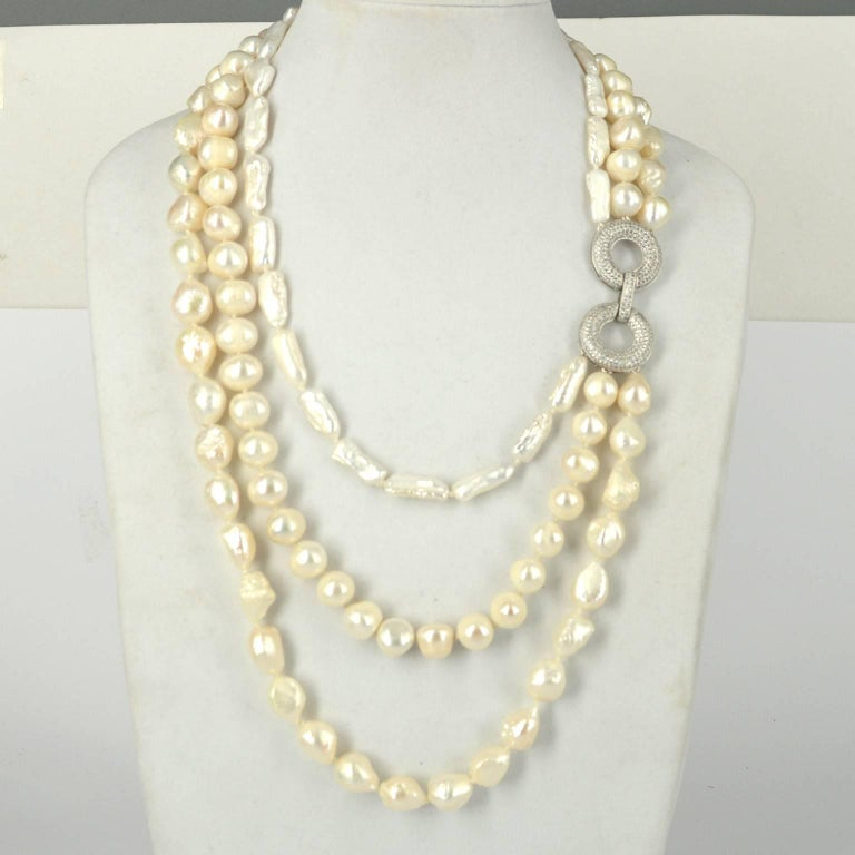 3 strands of white freshwater pearls in different shapes. Biwa pearl, baroque pearl and potato pearl. Pearls range from 10mm - 20mm Stunning CZ 925 Silver Rhodium plated feature clasp. Clasp can be worn to the side as shown or the back. Hand knotted