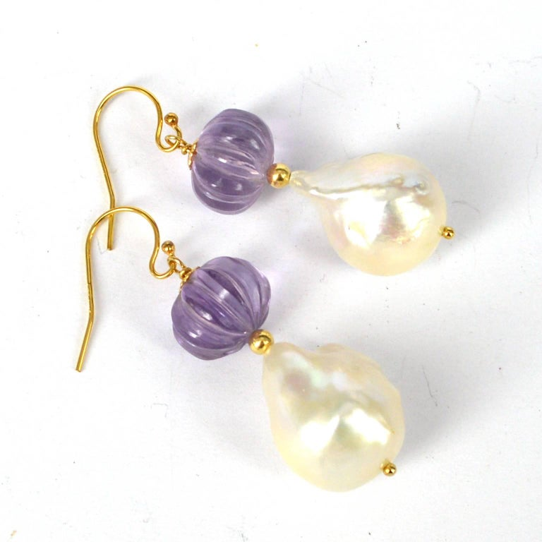 Stunning hand carved melon Shaped Amethyst with a high Quality Baroque Fresh Water Pearl. Amethyst Beads measure 10x9mm with a 14x18mm Pearl. All findings are 14k Gold Filled length of Earrings is 45mm