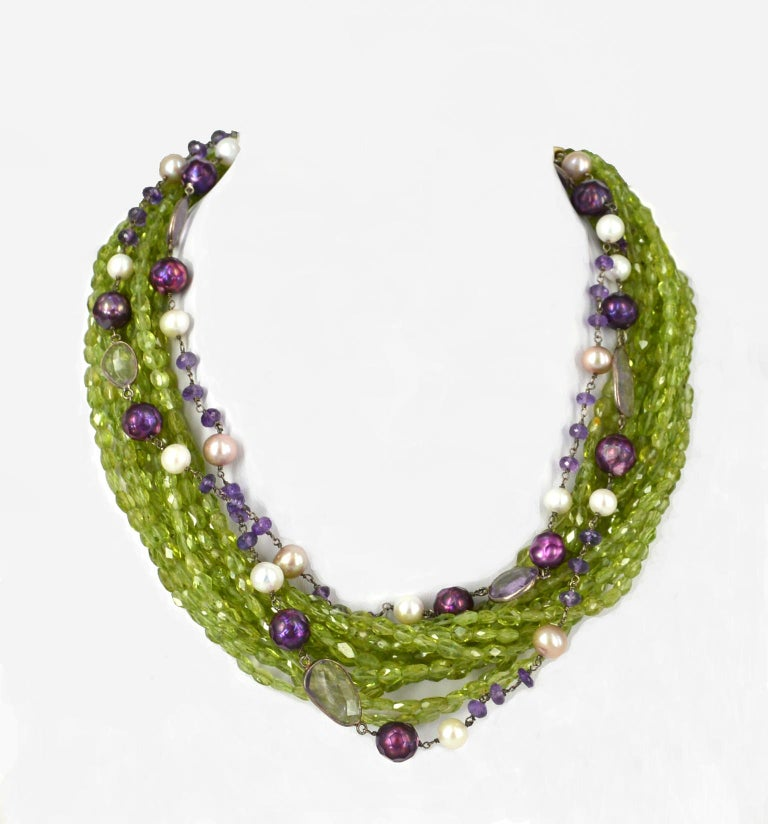 11 strands of faceted peridot 6x4mm beads with 2 strands of hand made link chain with Amethyst and Fresh Water Pearls finished with Gold plate Sterling Silver dome cap and 27mm hook clasp with a 10cm 14k Gold filled extension chain. Total length of