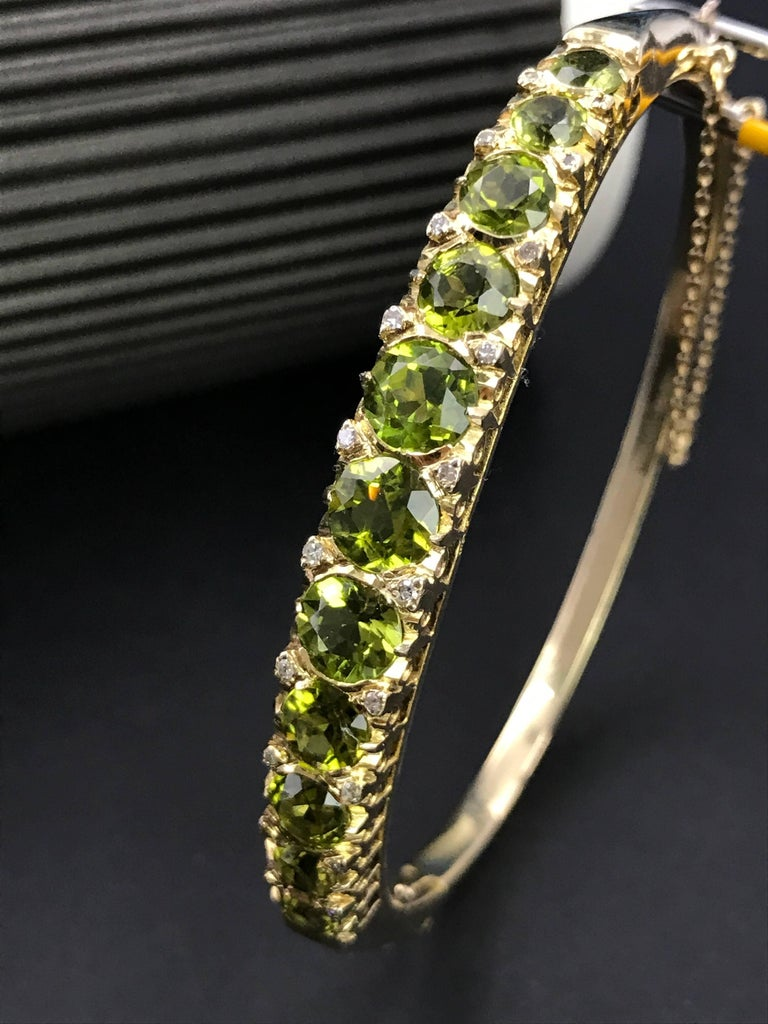 A Victorian 9 karat gold hinged bangle bracelet with peridot and diamonds. The bangle bracelet has 11 peridots with an approximate total weight of 5.3 carats set in a graduated line, 20 brilliant cut diamonds with an approximate total weight 0.5