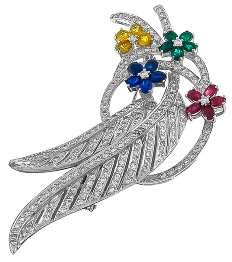 Made of 14k white gold, this pin is set with sparkling round cut diamonds  weighing approximately 4.00ct. The diamonds are accentuated by round and oval cut yellow sapphires, blue sapphires, emeralds and rubies that weigh approximately 7.50ct.