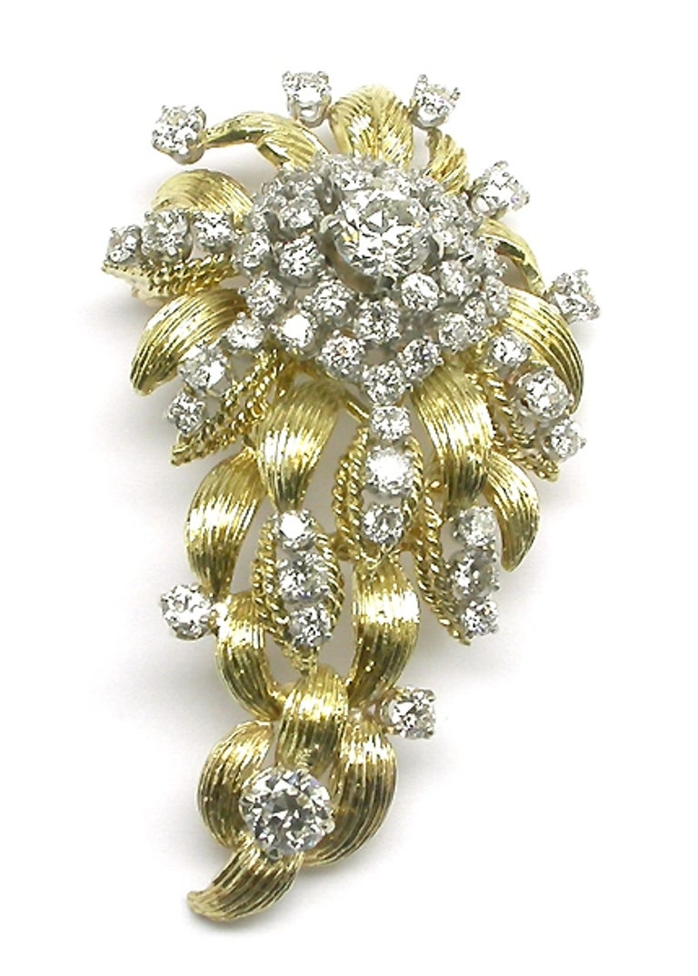 Made of 18k yellow gold, the pin features two sparkling old mine cut diamonds; one weighs approximately 1.10ct and the other weighs approximately 0.70ct. The color of these diamonds is G-I with SI1-SI2 clarity. These two diamonds are accentuated by