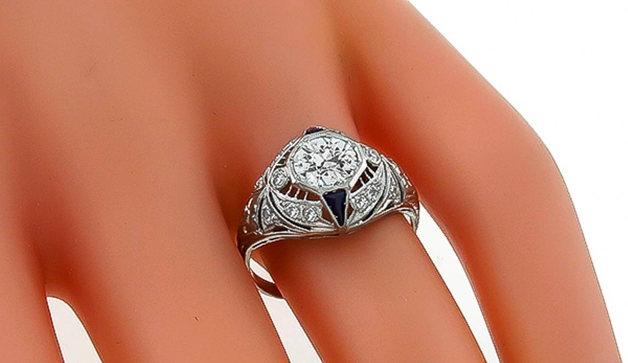 This fabulous platinum ring from the Art Deco era is centered with a sparkling GIA certified old European cut diamond that weighs 0.79ct. and is graded H color with VS1 clarity. The center diamond is accentuated by round cut diamond and trilliant