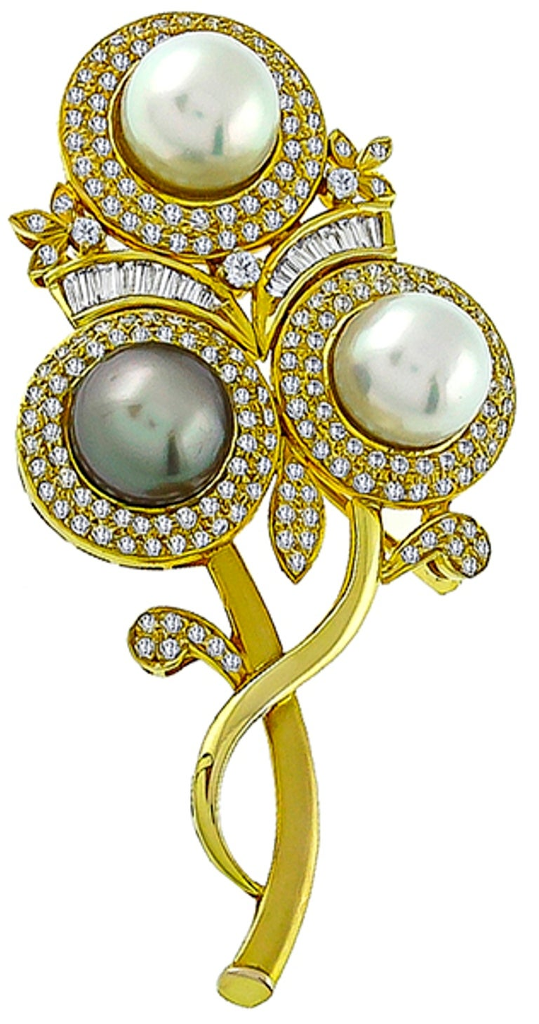 Made of 18k yellow gold, this pin features lovely white and gray south sea pearls which are accentuated by sparkling round and baguette cut diamonds that weigh approximately 4.00ct. The color of these diamonds is G with VS1 clarity.  