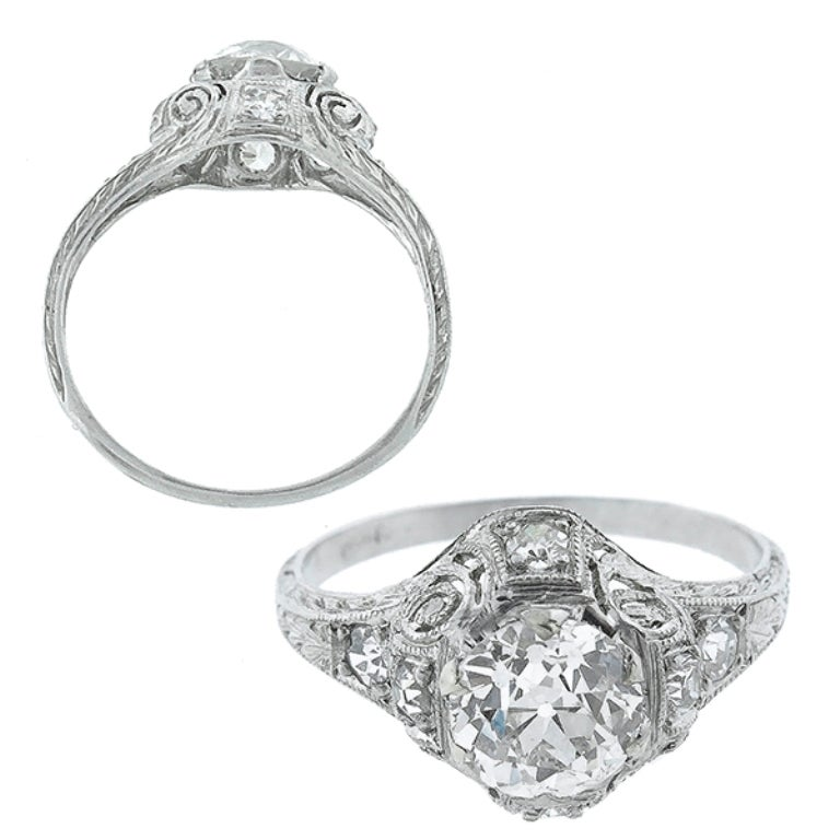 Handcrafted from the Edwardian era, this platinum ring centers a sparkling GIA certified old European cut diamond that weighs 1ct. and is graded G color with SI1 clarity. The top of the ring measures 11mm by 13mm.  The ring is size 5 1/2, and can
