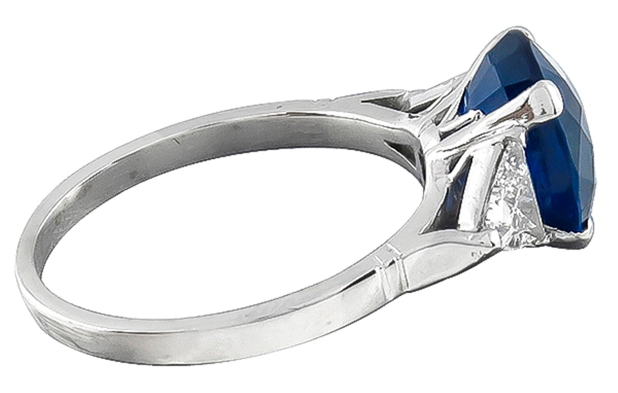 This gorgeous platinum ring centers a cushion cut vivid blue Ceylon sapphire that weighs 4.63ct. The center stone is flanked by sparkling trilliant cut diamonds weighing approximately 0.60ct. graded G-H color with VS clarity.