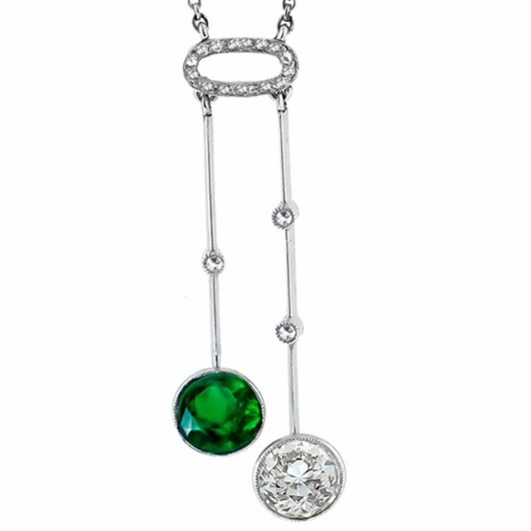 This beautiful platinum necklace from the Edwardian era, is set with a 1.28ct round cut Colombian emerald; and 1.09ct old mine cut diamond. The color of the diamond is I-J and VS1 clarity. The 2 sparkling center stone are accentuated by rose cut