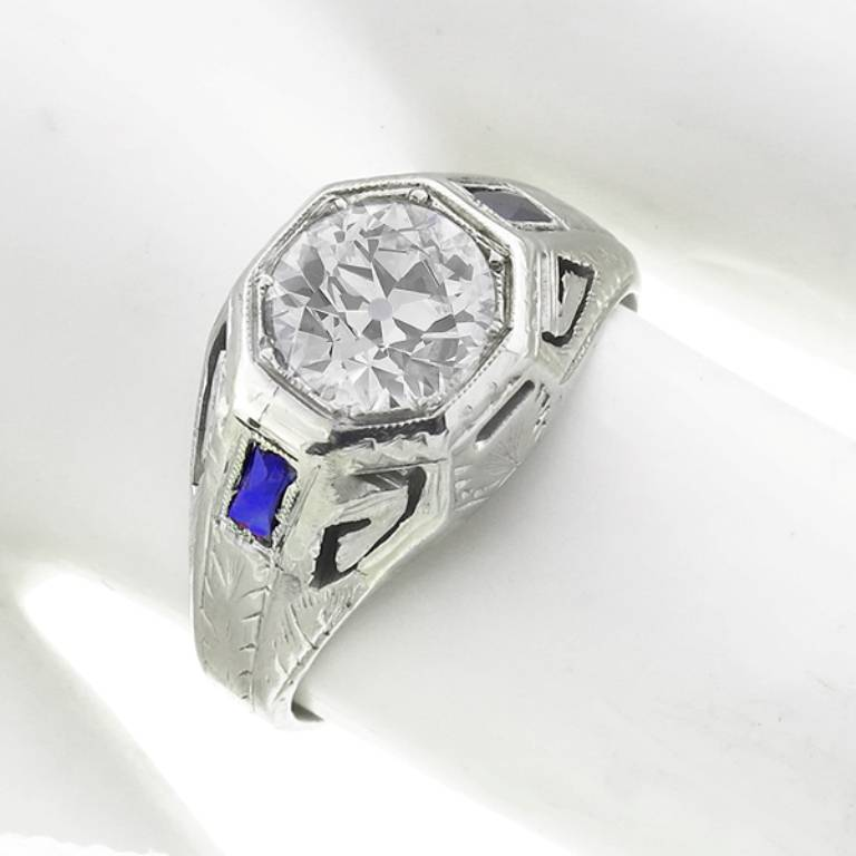 Made of 14k white gold, this ring centers an EGL certified old mine cut diamond that weighs 1.23 carat and is graded G-H color with SI1 clarity. The center stone is flanked by two faceted cut sapphires.  The size of the ring is 7 1/2, and can be