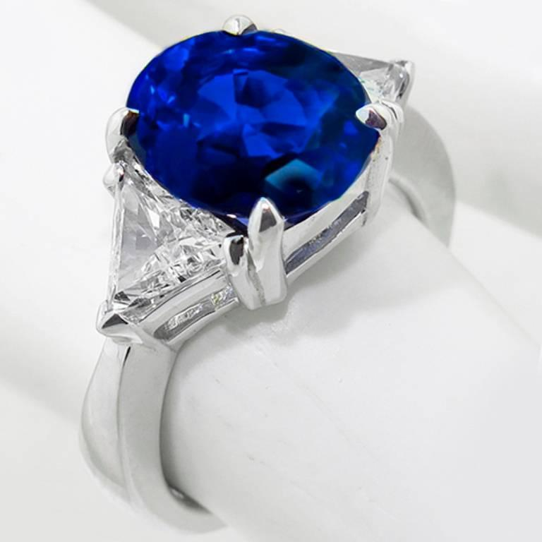 This stunning 14K white gold ring is set with a natural vivid blue oval cut sapphire that weighs 4.12ct. The sapphire is flanked by 2 sparkling trilliant cut diamonds that weigh approximately 0.75ct. graded H color with VS clarity.  The ring is