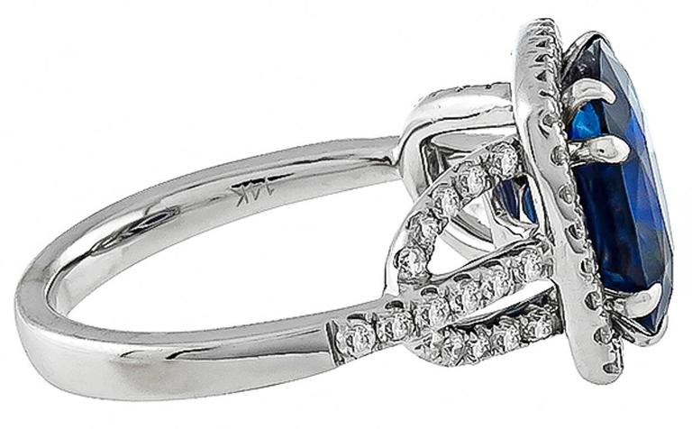 This amazing 14k white gold ring is centered with a gorgeous cushion cut sapphire that weighs 5.16ct. Accentuating the sapphire are sparkling round cut diamonds weighing approximately 1.00ct. graded H color with VS1 clarity. The top of the ring