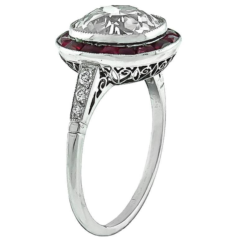 This stunning platinum engagement ring centers a sparkling old mine brilliant cut diamond that weighs 3.56ct. and is graded K color with VS2 clarity. Accentuating the center stone are french cut ruby accents and dazzling round cut diamond.