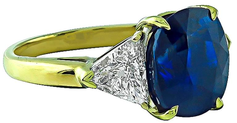 Made of 18k yellow gold, this ring is centered with a vivid blue cushion cut Ceylon sapphire that weighs 5.28ct. The center stone is flanked by sparkling trilliant cut diamonds that weigh approximately 1.00ct. and are graded G-H color with VS2