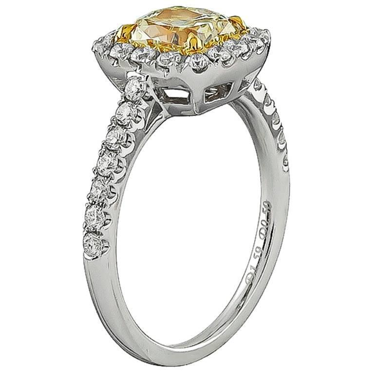 This amazing 18k white gold engagement ring is centered with a lovely radiant cut natural fancy yellow diamond that weighs 1.59ct. The clarity of the diamond is VS1. Accentuating the center stone sparkling round cut diamonds that weigh approximately