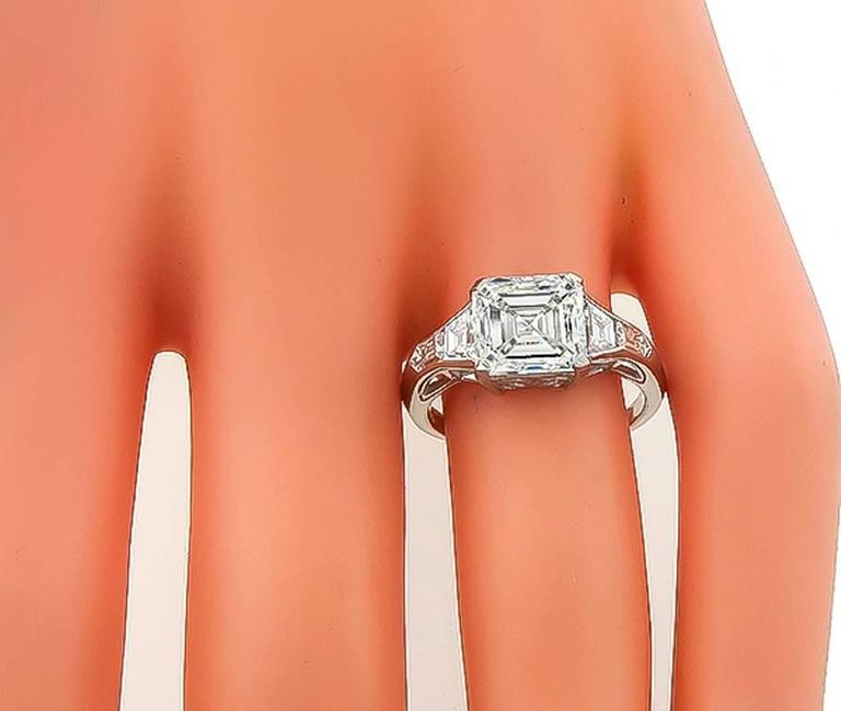 This elegant platinum ring is centered with a sparkling GIA certified square emerald cut diamond that weighs 3.01ct. graded J color with VS1 clarity. The center stone is flanked by high quality shield and trapezoid cut diamonds that weigh