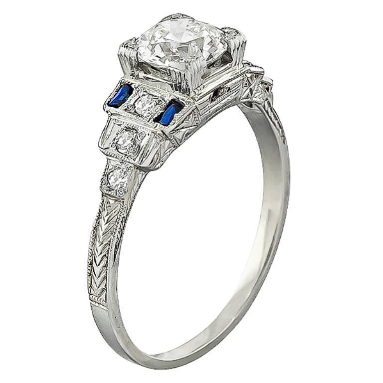 Made of 14k white gold, this ring is centered with a sparkling GIA certified old mine cut diamond that weighs 0.90ct. graded K color with SI2 clarity. The center diamond is accentuated by lovely sapphire and diamond accents. It is size 8 but it can