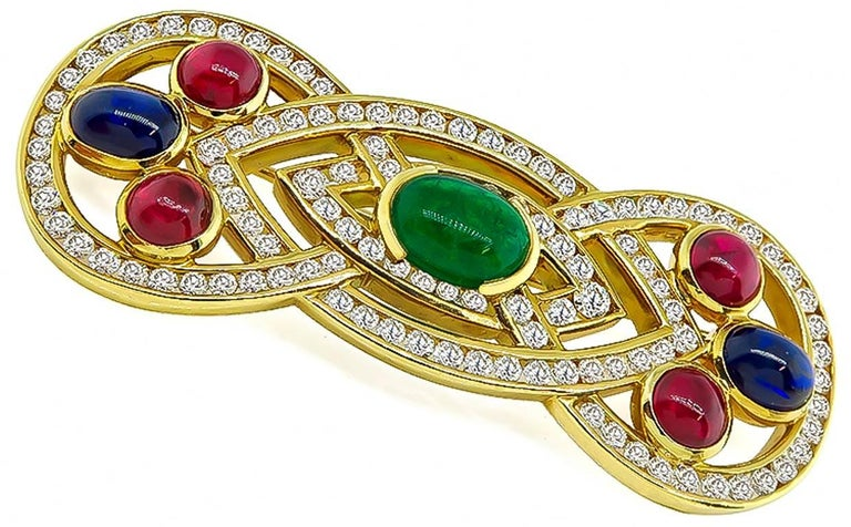 This charming 18k yellow gold pin is set with cabochon emerald, ruby and sapphire that weighs approximately 1.25ct, 2.00ct and 2.00ct respectively. The colored stones are accentuated by sparkling round cut diamonds that weigh approximately 2.50ct.