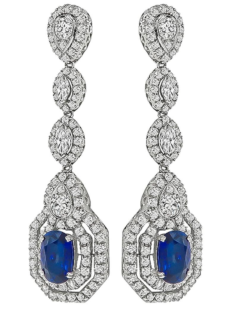 This fabulous pair of 18k white gold drop earrings feature cushion cut sapphires that weigh approximately 5.85ct. The sapphires are accentuated by sparkling marquise, old mine and round cut diamonds that weigh approximately 5.88ct. The color of