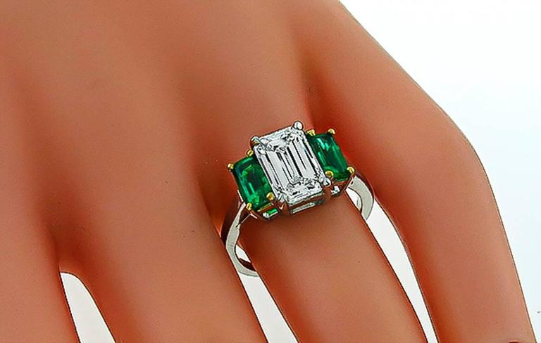 This elegant platinum engagement ring is centered with a sparkling GIA certified emerald cut diamond that weighs 2.27ct. and is graded H color with SI1 clarity. The center diamond is flanked by two emerald cut Colombian emeralds that weigh