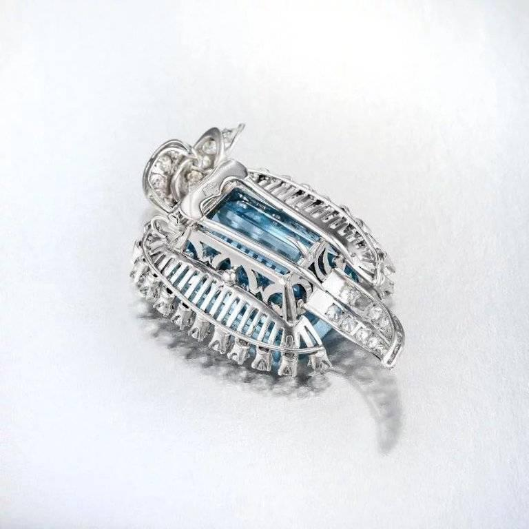 This impressive brooch set in platinum features a modified rectangular-cut high quality blue aquamarine weighing approximately 23.00 carats. The aquamarine is enhanced by round brilliant-cut diamonds weighing a total of approximately 1.55 carats,