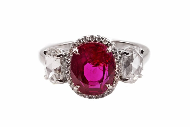Classic contemporary luxurious Burma ruby and rose cut diamond three stone ring mounted in platinum. This extremely fine hand crafted ring in platinum contains an oval brilliant cut natural Burmese ruby with strong saturated pinkish red color. The