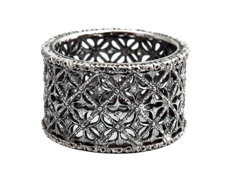 Mario Buccellati 18 karat white gold and diamond band exquisitly hand crafted with impecable ajour and engraving work. Small round cut diamonds are set throughout this band giving it some sparkle with every movement of the hand. This craftsmanship,