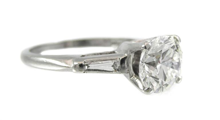 A platinum mounting displaying a beautiful sparkling 2 carat round brilliant diamond shouldered by a bright white tapered baguette on either side creates an elegant ring perfect for everyday wear.  - Round brilliant cut diamond weighing 2.00cts -