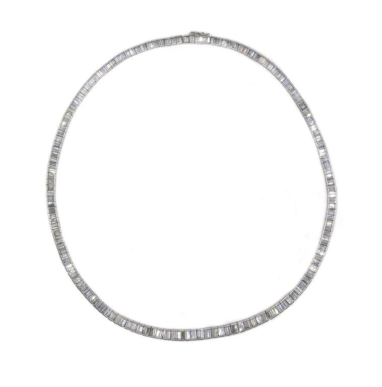 This impressive platinum 17 inch long riviere necklace is set with 333 baguette cut diamonds with an approximate total weight of 20 carats. This flexible and finely hand crafted necklace falls elegantly around every neck showing off a river of white