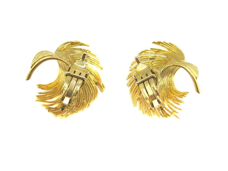 These glamorous 18 Karat gold Tiffany & Co ear clips from the 1960's have a unique design, in the shape of feathers, finely handcrafted from strings of curved gold wires. The ear clips are most flattering on any ear and are light enough for a