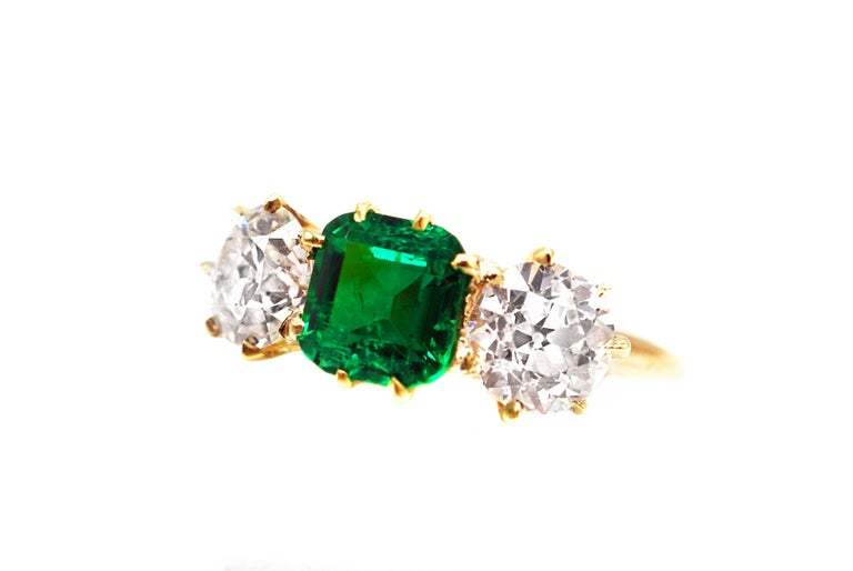 This unique Belle Epoque, ca. 1980 Colombian emerald diamond 3 stone ring, features one centrally set beautiful forest green emerald weighing 1.18 carats. The emerald is accompanied by a report from the AGL stating that the origin is Columbia and