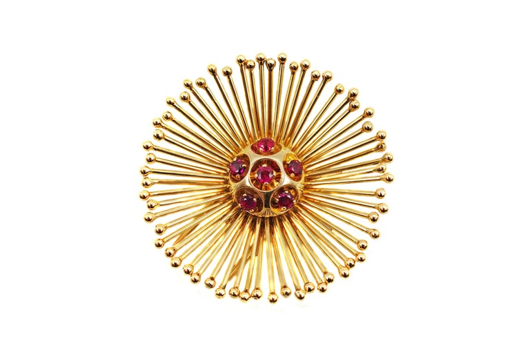Exquisite suite of 1950s Retro Cartier Paris 18 karat yellow gold and ruby ear clips and brooch. The finely hand-crafted pieces by the renown jewelry house of Cartier guarantees the highest quality of craftsmanship and design. The starburst design,