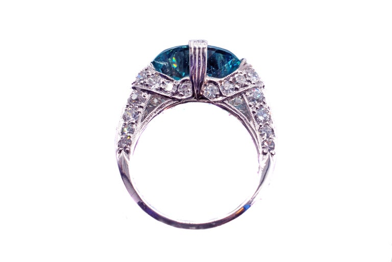 This enticing Art-Deco platinum diamond blue zircon ring from ca. 1930 features amazing craftsmanship and design. The centrally set 8.94 carat zircon is incredibly clear and displays an electric deep aqua blue color distinct to these unique