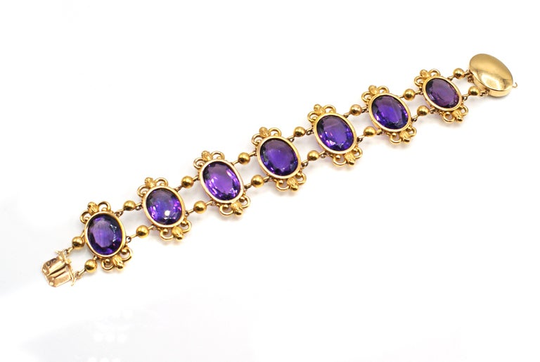 Gorgeous antique French Amethyst 18 karat yellow gold flexible link bracelet from ca. 1880. Seven beautiful, lively and sparkling deep violet Amethysts are the center pieces of this lovely bracelet. Perfectly matched in color and cut these gemstones