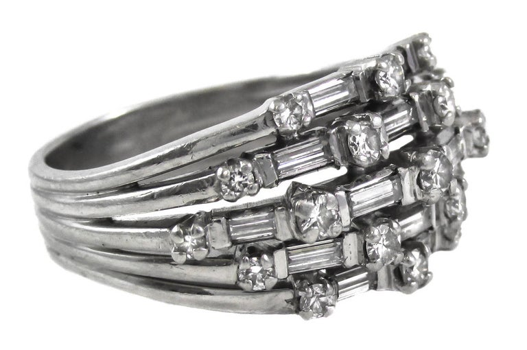 Handcrafted in platinum, this stunning ring is set with alternating beautiful white bright sparkly round brilliant cut and baguette cut diamonds. The central band of diamonds is flanked by 2 graduating rows on either side, giving this ring an