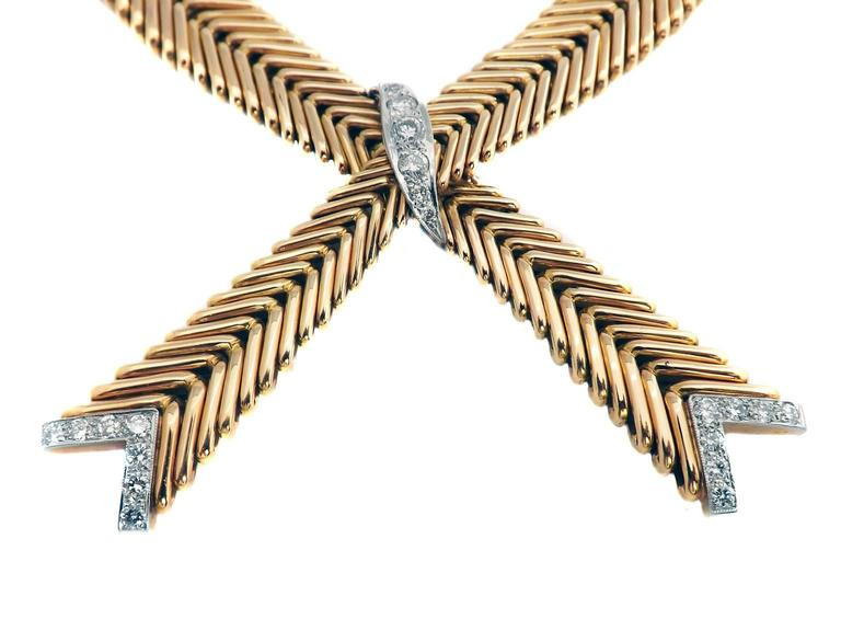 French Retro 18 karat yellow gold and diamond herringbone crossover necklace. Two herringbone chains connected by a wave of diamonds set in platinum that descend in size from the center to the ends with fine milgrain along the perimeter. The ends of