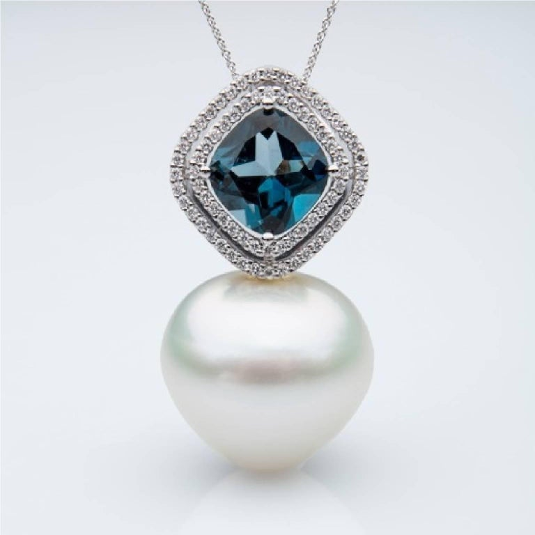 Stunning and bold London Topaz pendant, surrounded with 0.30 carat white diamonds.    This pendant is perfectly balanced with an 18.2mm triangular shaped white, grade 1, fine nacer, high luster, white pink color, Australian South Sea pearl.   The