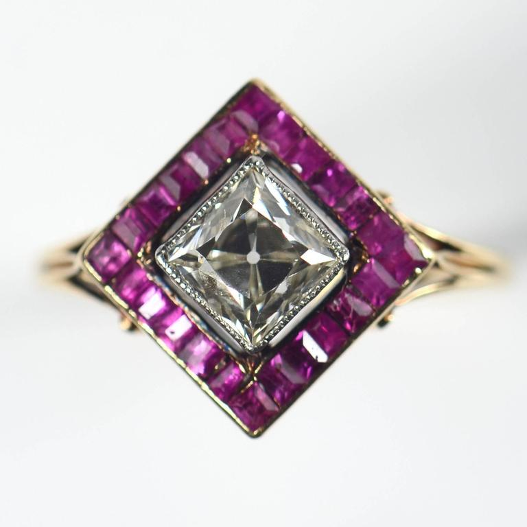 An unusual and very elegant Edwardian ruby and diamond cluster ring, set with a 1.20 carat old mine cut diamond, surrounded by calibre cut rubies.  The gold shank is bifurcated and scrolls up to meet the pierced gallery of the head of the ring.  The