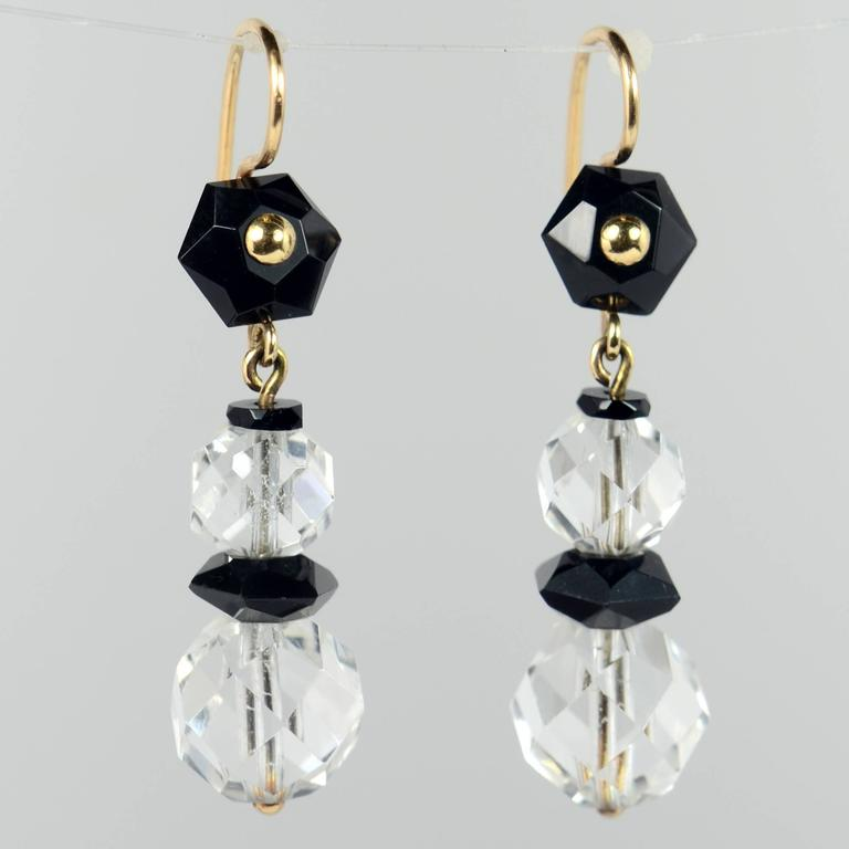 A stylish pair of earrings from the Art Deco period with faceted beads of rock crystal and black onyx suspended from 14 carat yellow gold wires. Very easy and elegant to wear.  The earrings are 4.2cm in length and are 1.1cm wide, and weigh 6.62g in