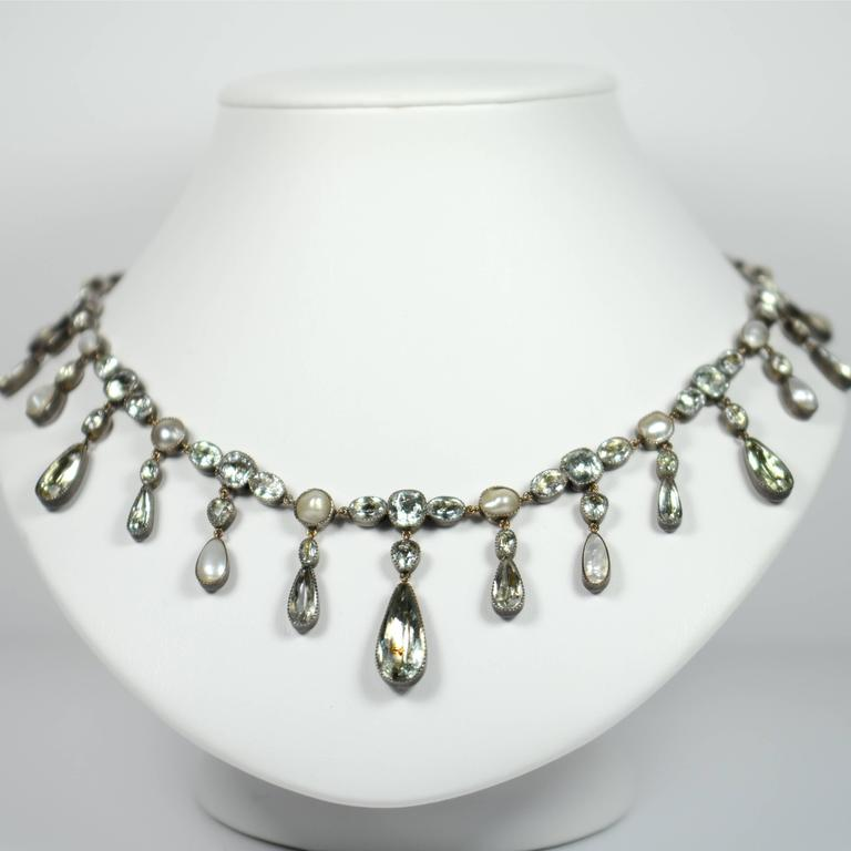 A rare and extremely pretty Georgian fringe riviere necklace with 63 foiled aquamarines and 18 blister pearls millegrain set to closed back silver mounts with a gold chain and toggle clasp.   The graduated fringe pendant drops alternate between
