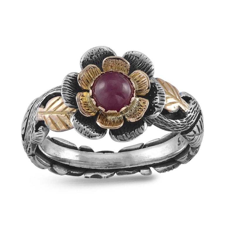 This lovely one of a kind ring has been handmade in our workshops. It has a central cabochon ruby, surrounded by intricate 18 karat yellow gold and oxidised hand engraved silver work in the shape of leaves and flowers. A stylish, adorable ring. 10mm
