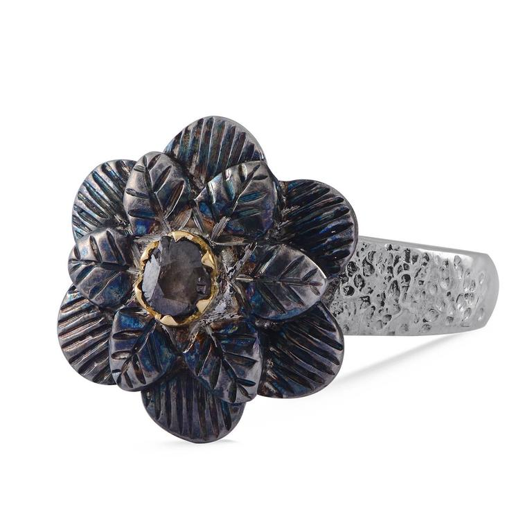 This lovely ring has been exquisitely made by our master goldsmtihs, using our signature engraving work. The central rose cut diamond is set in 18 karat gold and embedded in a beautiful flower motif. The ring is made in oxidised silver and has a